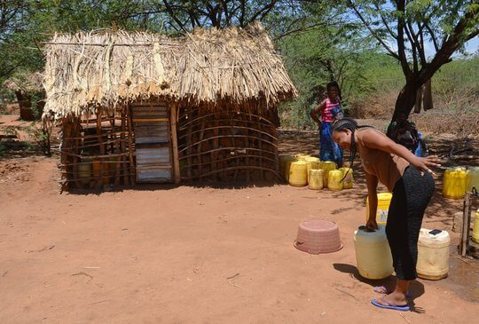 Frau mit Wasserkanister vor Hütte in Kenia